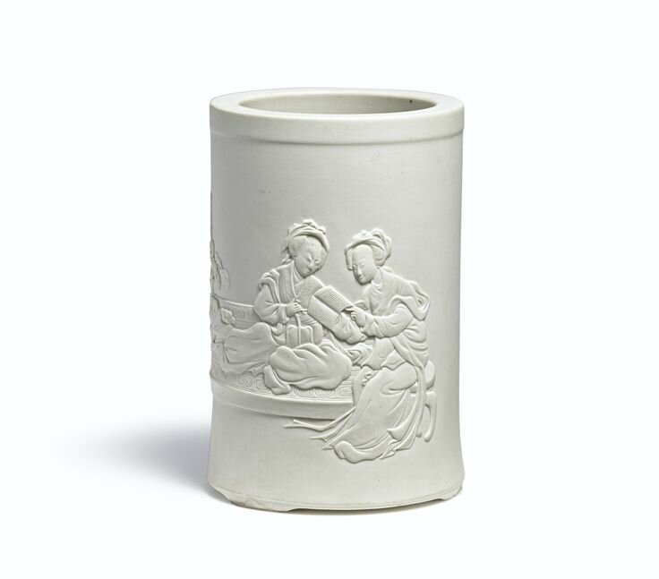 A fine and rare carved white biscuit 'Two Qiaos' brushpot, Qing dynasty, Kangxi period