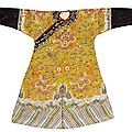 A yellow silk ground embroidered dragon robe. 19th century