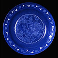 Fritware dish, with decoration cut through a blue slip under a transparent glaze. Iran, Kerman?; 17th century