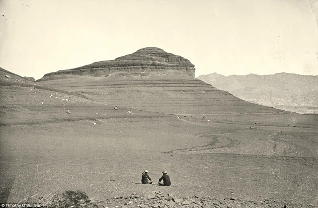Two men sit looking at headlands north of the Colorado River Plateau in 1872