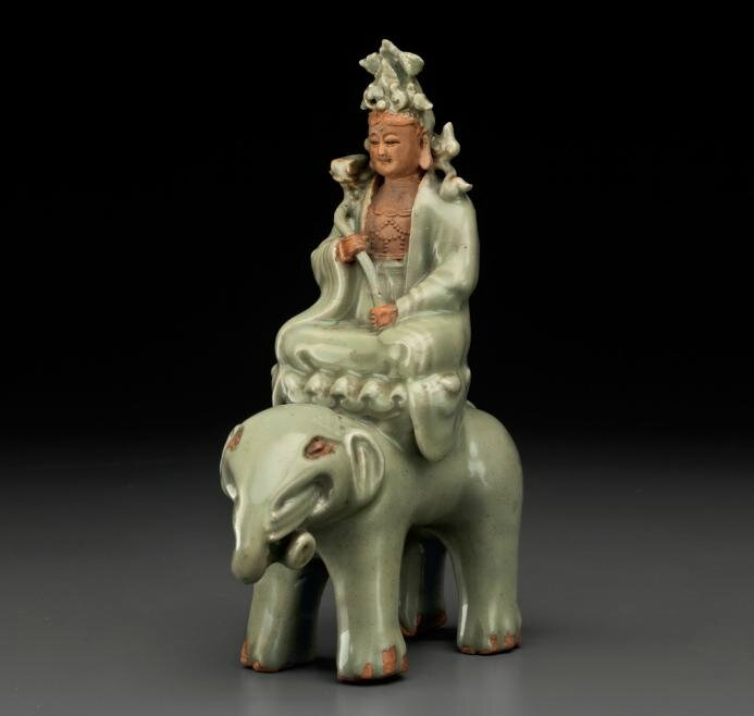 A rare Longquan celadon figure of Puxian seated on an elephant,Ming dynasty, 14th-15th century