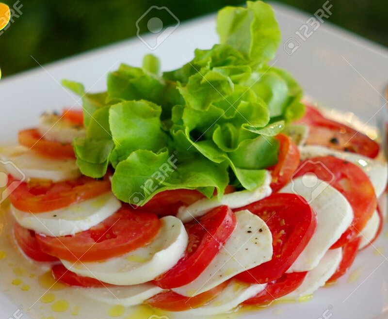 6010261-a-salad-of-tomato-lettuce-and-mozzarella-dressed-and-on-a-serving-plate-shallow-depth-of-field-and-a