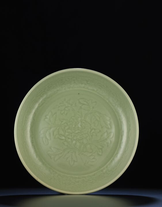 A rare finely carved early Ming Longquan celadon dish, Ming dynasty, early 15th century