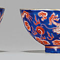 A pair of iron-red and blue-enameled dragon cups, jiaqing four-character seal marks in iron red and of the period (1796-1820)