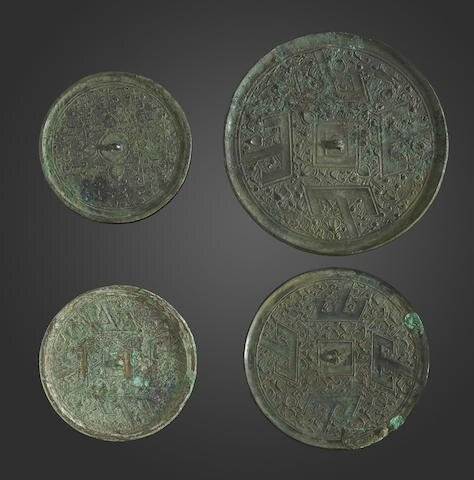 A group of four early bronze mirrors, Warring States period