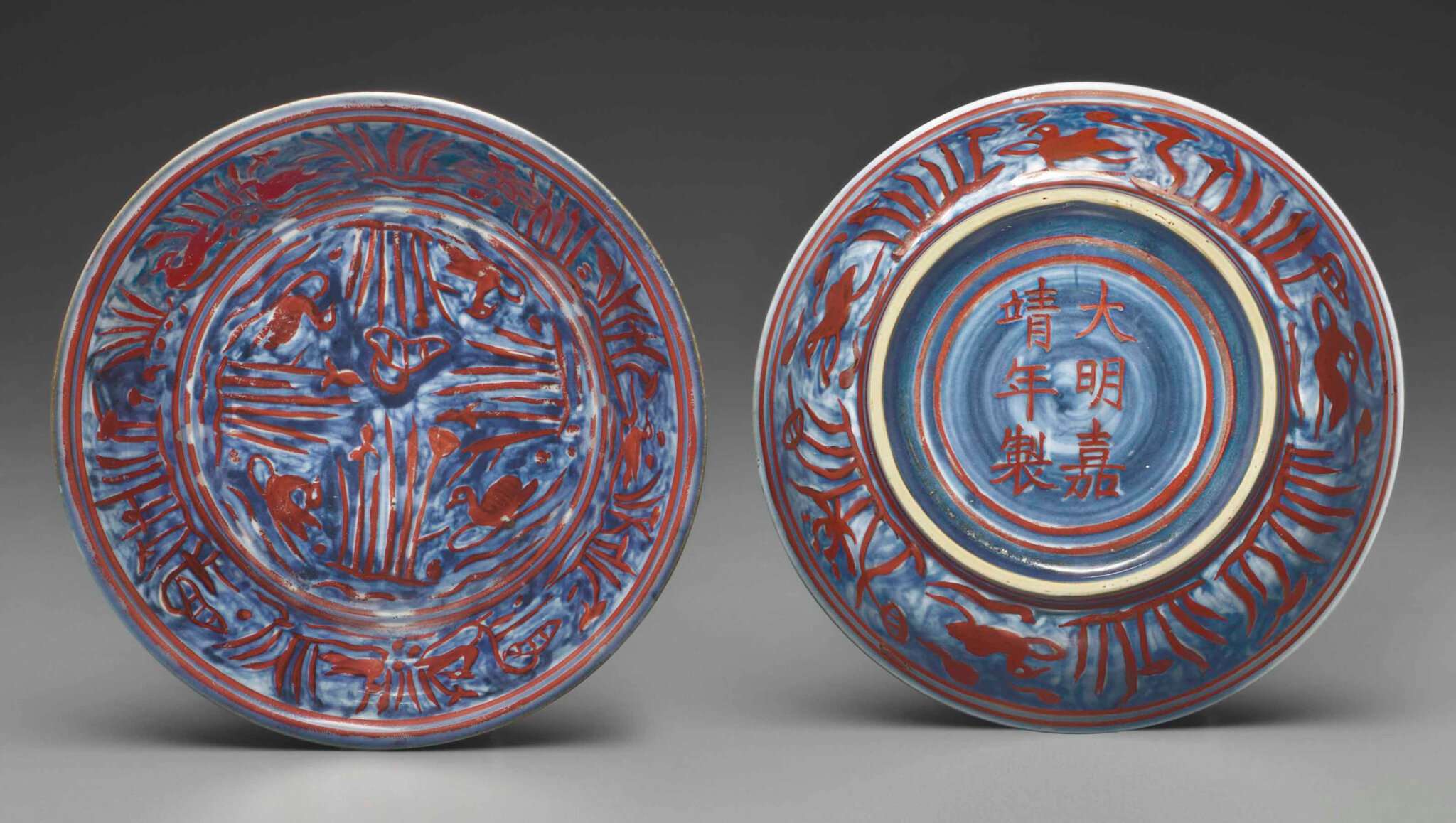 A very rare pair of small iron-red decorated blue and white dishes, Jiajing iron-red six-character marks within double-circles and of the period (1522-1566)