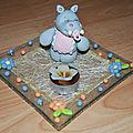 Une assiette en verre décorée avec un hippo et des fleurs en porcelaine froide qui permet d'y mettre une petite bougie.