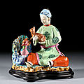 A polychrome porcelain group of a seated woman holding a dog, qing dynasty, qianlong period (1736-1795)