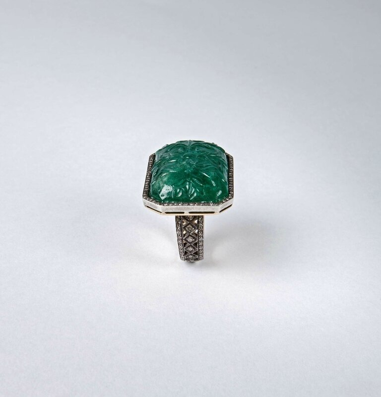 A carved emerald ring set in white gold with pave diamonds
