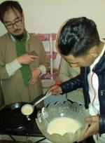 Farid verse la pâte sous le regard de Kato