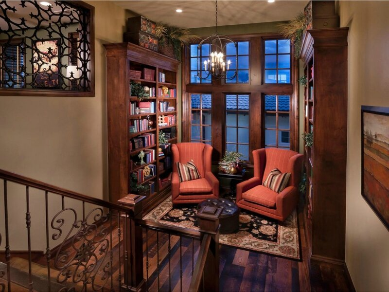 traditional-small-living-room-design-with-brown-varnishes-pine-wood-wall-library-shelves-and-classic-chandelier-over-double-orange-fabric-wingback-chairs-also-brown-round-