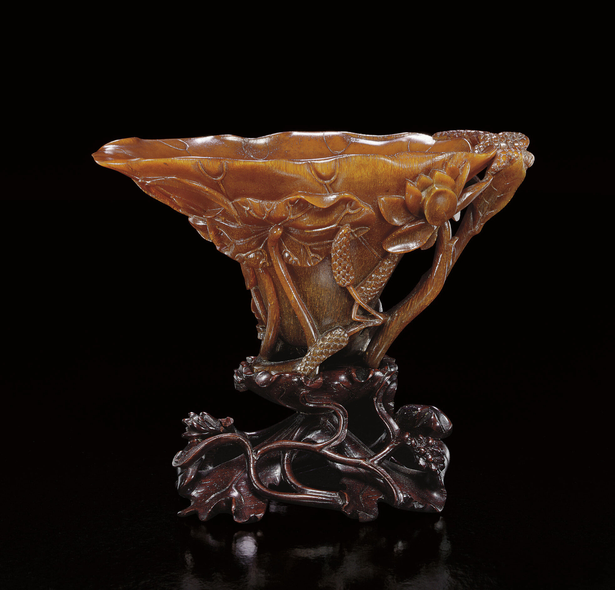 A finely carved 'Lotus-leaf' rhinoceros horn libation cup, Ming dynasty, 17th century