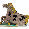 A rare aubergine, yellow, black and green-glazed biscuit figure of a recumbent horse, qing dynasty, kangxi period (1662-1722)