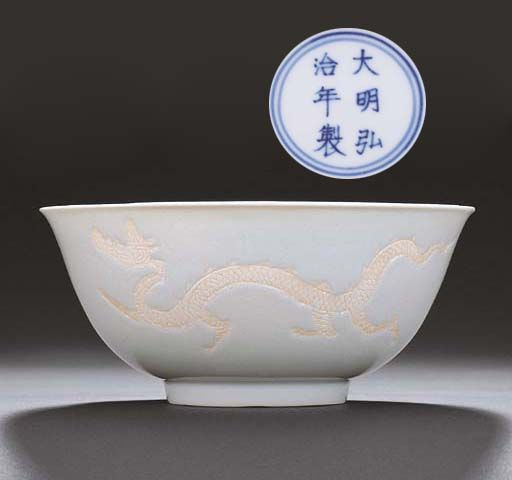 A rare Ming white-glazed and biscuit-decorated 'Dragon' bowl, Hongzhi six-character mark within double-circles and of the period (1488-1505)
