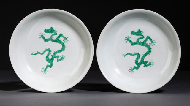 A rare pair of green-enamelled dragon anhua wave dishes, underglaze blue Hongzhi six-character marks and probably of the period