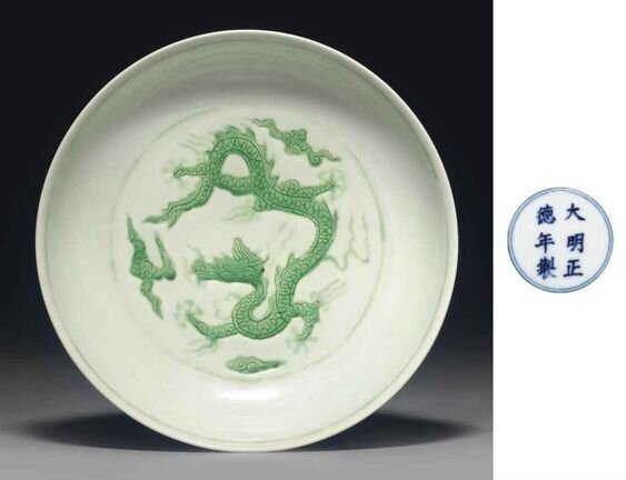 A_green_glazed_incised__dragon__dish__Zhengde_six_character_mark_in_underglaze_blue_within_a_double_circle_and_of_the_period__1506_1521_