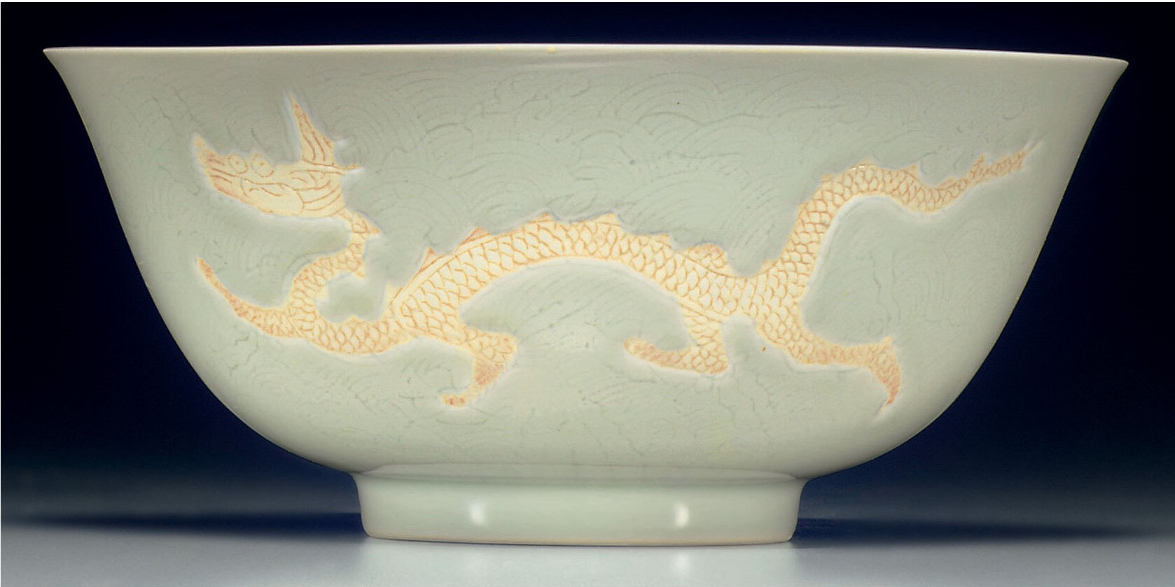 A rare biscuit-decorated white-glazed 'dragon' bowl, Hongzhi six-character mark within a double-circle and of the period (1488-1505) (2)